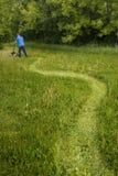 Man med gräsklipparen som mejar högväxt gräs och stor stor gräsmatta Fotografering för Bildbyråer