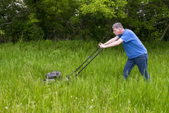 Man med gräsklipparen som mejar högväxt gräs och stor stor gräsmatta Royaltyfria Bilder