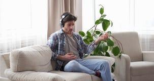 Man med hörlurar som sjunger och spelar Air Guitar arkivfilmer
