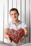 Man med hand-gjort rött hjärtasammanträde nära väggen royaltyfri foto
