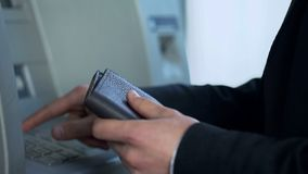Man med handväskan som sätter in kortet i ATM för att återta kassa och motta jämviktsrapporten royaltyfri fotografi