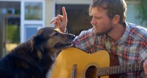 Man med hans hund som spelar gitarren i trädgården 4k lager videofilmer