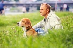 Man med hans hundsammanträde i grönt gräs royaltyfri bild