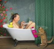 Man med hans katt i badrummet arkivbild
