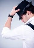 Man med hatten på grå bakgrund arkivfoto