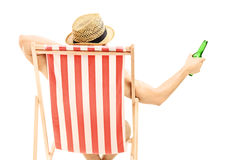 Man med hattsammanträde på en strandstol och innehav en ölflaska Royaltyfri Bild