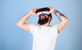 Man med hipsterskägget som tycker om digitalt techkrimskrams Hållande ögonen på film för upphetsad skäggig man i VR-exponeringsgl arkivbild