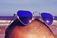 Man med hjärta-formad solglasögon på stranden, med en retro effe Arkivbild