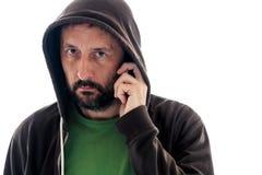 Man med hoodien genom att använda mobiltelefonen royaltyfria foton