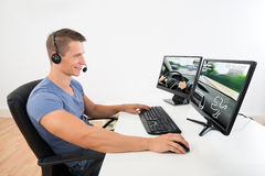 Man med hörlurar med mikrofon som spelar leken på datoren Fotografering för Bildbyråer