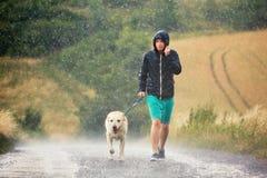 Man med hunden i hällregn royaltyfri bild