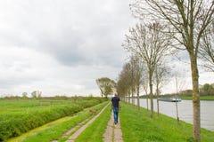 Man med hunden i holländskt landskap Royaltyfria Bilder