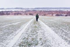 Man med hunden på den snöig vägen arkivbilder