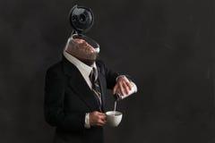 Man med huvudet i en kaffekruka Arkivbild
