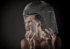 Man med huvudet inom en fågelbur royaltyfri fotografi