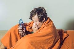 Man med influensa- eller förkylningtecken som gör inandning med nebulizeren - royaltyfri fotografi