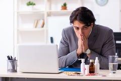 Man med influensa som arbetar i kontoret arkivfoton