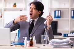 Man med influensa som arbetar i kontoret arkivbilder