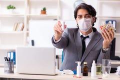 Man med influensa som arbetar i kontoret royaltyfri fotografi