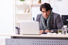 Man med influensa som arbetar i kontoret arkivbild