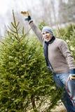 Man med julgranen på en lantgård Arkivbild