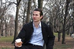 Man med kaffe i park Arkivbild