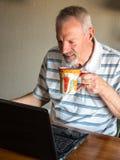 Man med kaffe och hans dator Arkivfoton