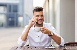 Man med kaffe som kallar på smartphonen på stadskafét Royaltyfri Bild