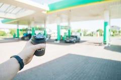 Man med kaffekoppen som går till hans bil på bensinstation royaltyfria foton