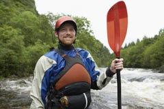 Man med kajakåran mot floden Royaltyfria Foton