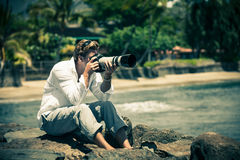 Man med kameran och en Zoom Lens Arkivbild