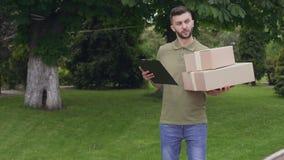Man med kartongen som söker efter höger adress för att leverera lager videofilmer