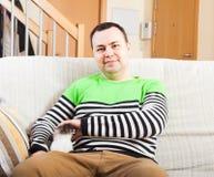 Man med kattungen på soffan arkivfoto