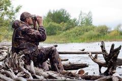 Man med kikare i jakten Fotografering för Bildbyråer