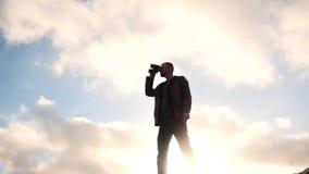 Man med kikare mot solsikt stock video