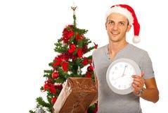 Man med klockan för jultomtenhattinnehavet arkivfoto