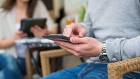 Man med klockan genom att använda smartphonen, närbild. Arkivbild