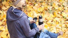 Man med koppen av den varma drinken - te eller kaffe och termoset sitter i höstskog med ryggsäcken, bakre sikt arkivbild