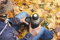 Man med koppen av den varma drinken - te eller kaffe och termoset sitter i höstskogen, bästa bakre sikt royaltyfria bilder