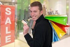 Man med kreditkort- och shoppingpåsar i en shoppa royaltyfria foton