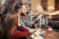 Man med kreditkorten genom att anv?nda betalningterminalen p? restaurangen royaltyfria bilder
