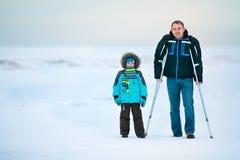 Man med kryckor och hans son som utomhus går Royaltyfria Bilder