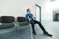 Man med kryckor som sitter på stol Arkivfoton