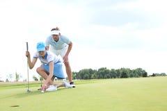 Man med kvinnan som siktar bollen på golfbana mot himmel royaltyfri fotografi