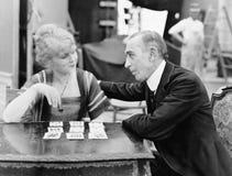 Man med kvinnan som spelar kortspelet (alla visade personer inte är längre uppehälle, och inget gods finns Leverantörgarantier so Arkivbild