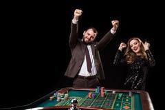 Man med kvinnan som spelar rouletten på kasinot Böjelse till Arkivfoton