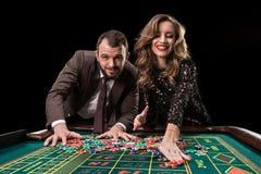 Man med kvinnan som spelar rouletten på kasinot Böjelse till Royaltyfri Bild