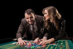 Man med kvinnan som spelar rouletten på kasinot Böjelse till royaltyfria bilder