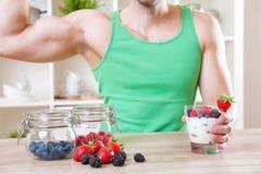 Man med läcker yoghurt med nya bär arkivfoton