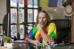 Man med långt hår i ett färgrikt kontor Arkivbilder